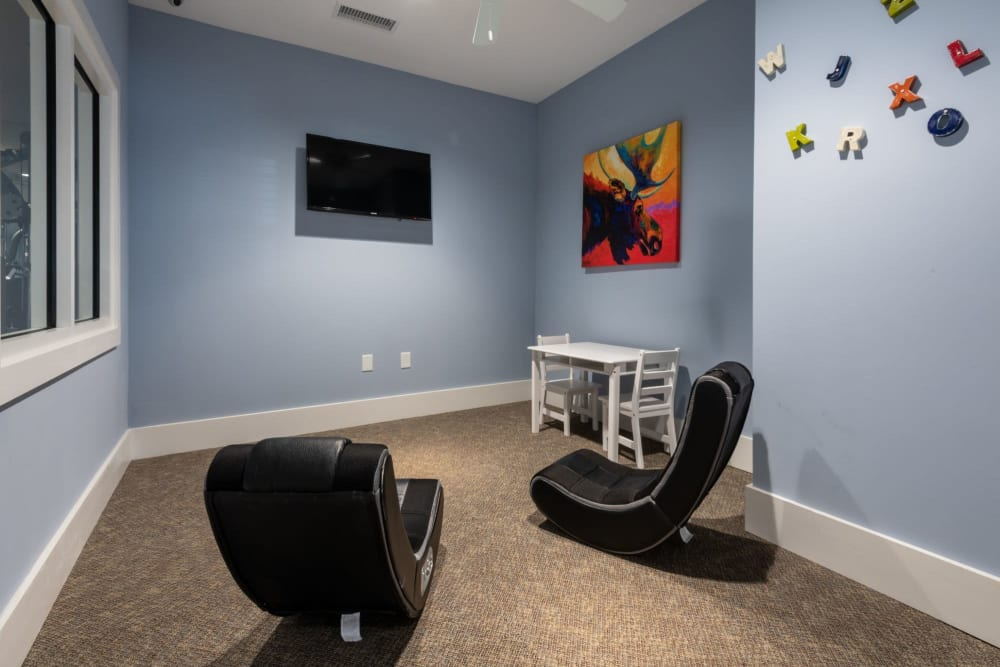 Kids area with a tv and chairs at The Reserve at White Oak in Garner, North Carolina