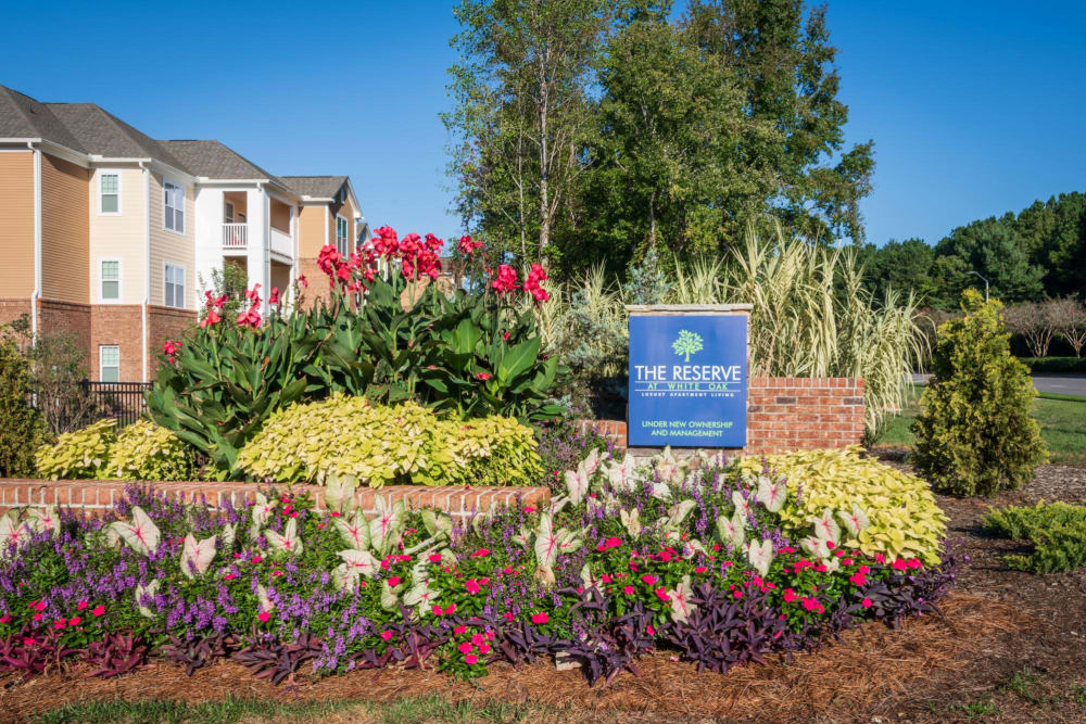 Exterior welcoming sign surrounded by tons of flowers at The Reserve at White Oak in Garner, North Carolina