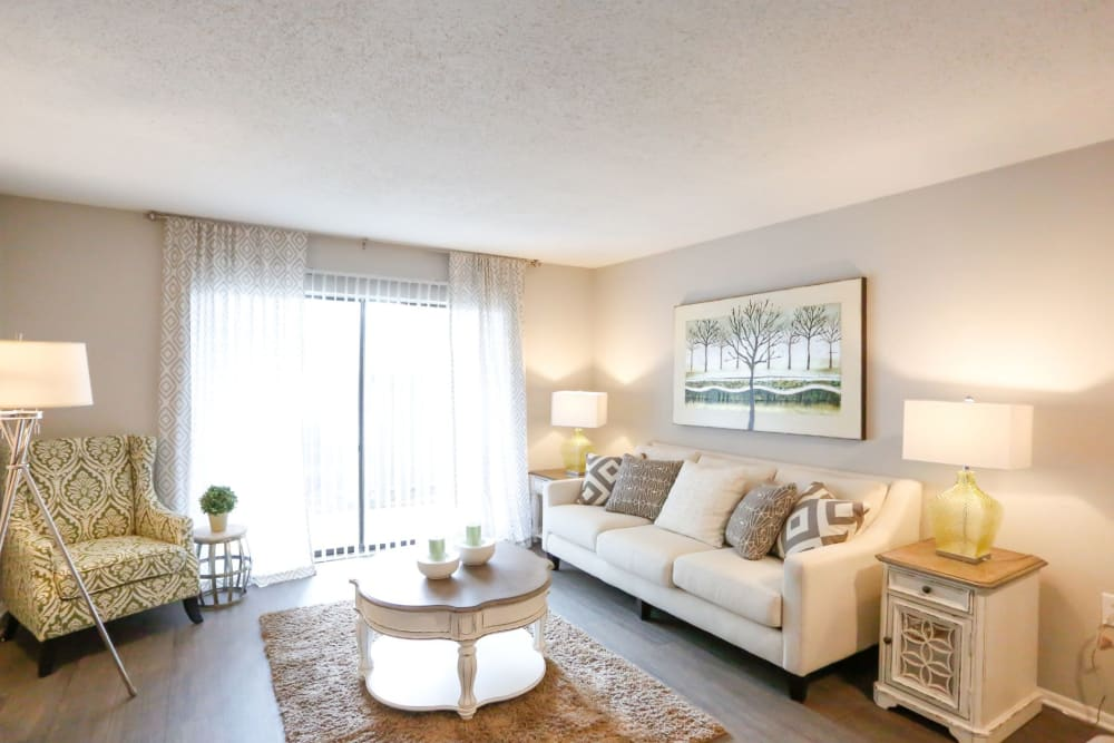 Spacious living room with floor to ceiling glass doors in model home at The Flats at Arrowood in Charlotte, North Carolina