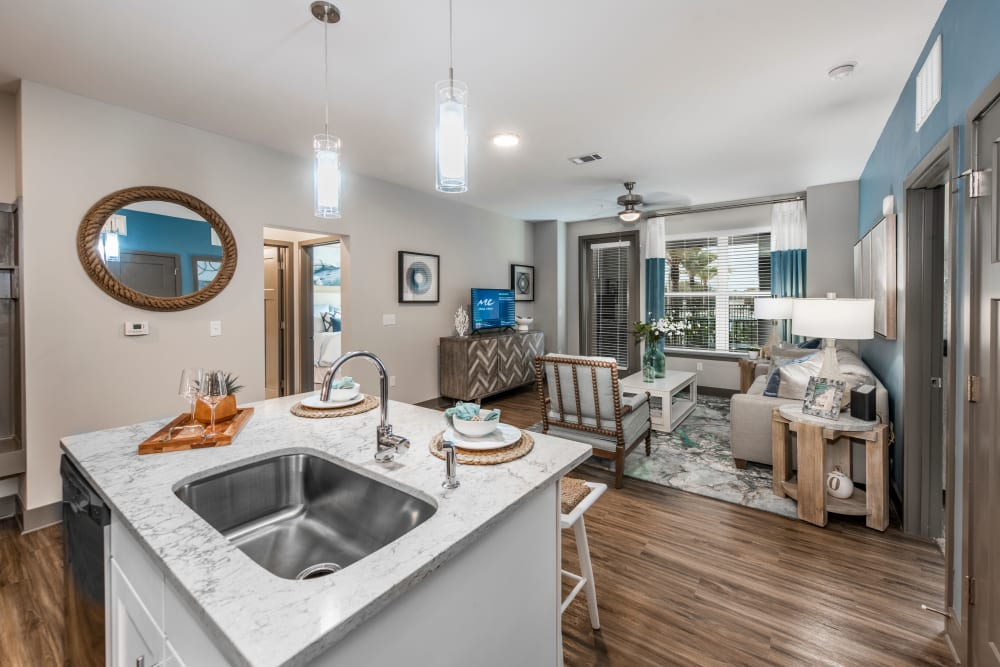 An open-concept floor plan with the kitchen overlooking the living room at Olympus Emerald Coast in Destin, Florida