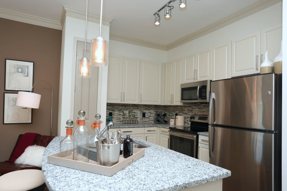 Stainless-steel appliances and an island in a model apartment's kitchen at 2370 Main at Sugarloaf in Duluth, Georgia