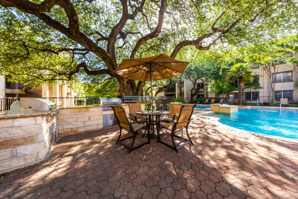 Outdoor BBQ area with covered tables and chairs at Marquis at Ladera Vista in Austin, Texas