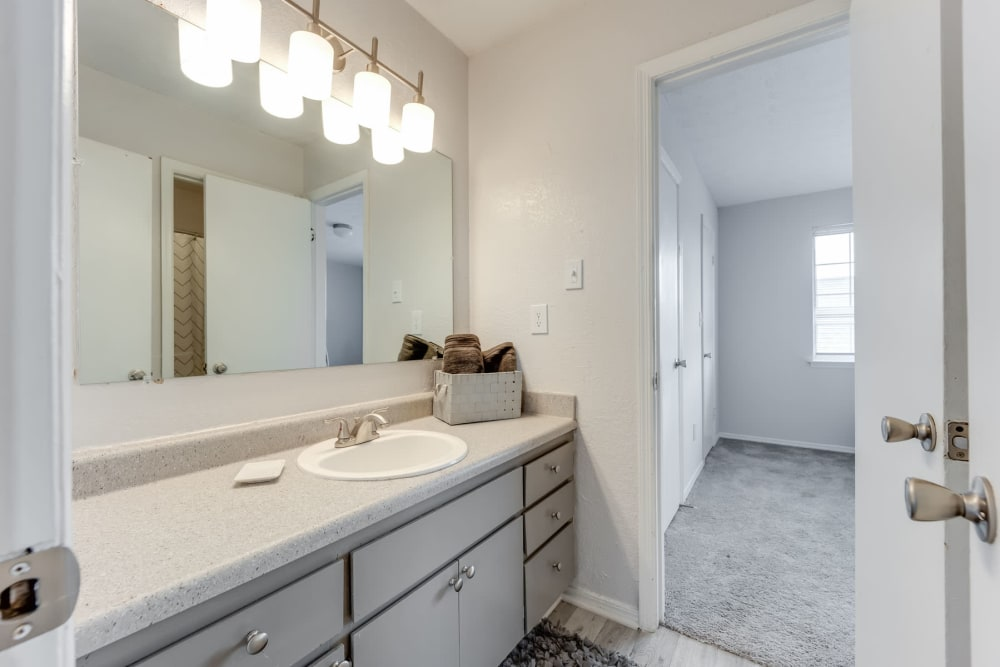 Ample countertop space and a large vanity mirror in an apartment home's bathroom at Sedgefield in Marietta, Georgia