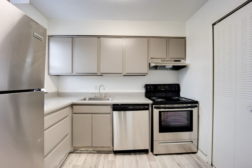 Modern kitchen with hardwood-style flooring and stainless-steel appliances in an apartment at Sedgefield in Marietta, Georgia