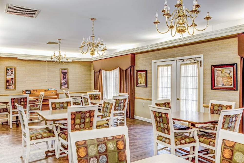 Community dining area with elegant chandeliers and wall drapes at Carriage Court of Washington Court House in Washington Court House, Ohio