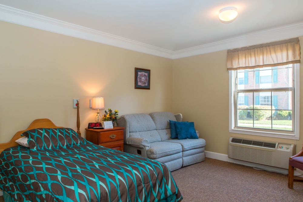 Upscale bedroom in senior living facility with sofa seating and window light at Carriage Court of Washington Court House in Washington Court House, Ohio