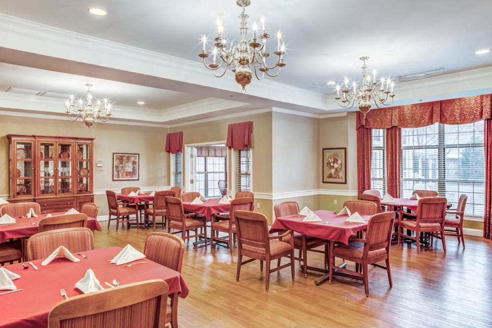 Ornate dining room  with wood accents and chandeliers at Carriage Court of Lancaster in Lancaster, Ohio