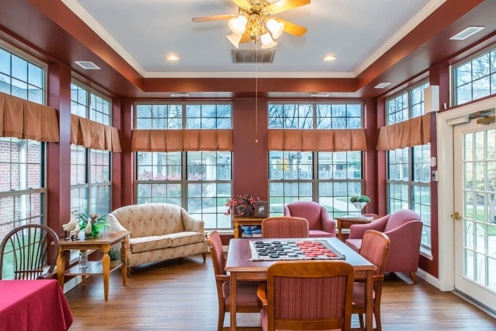 Cozy sitting room with wood accents, armchair seating, and chess set at Carriage Court of Lancaster in Lancaster, Ohio