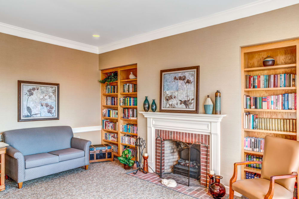 Sitting area complete with wood bookshelf and cozy fireplace at Carriage Court of Lancaster in Lancaster, Ohio