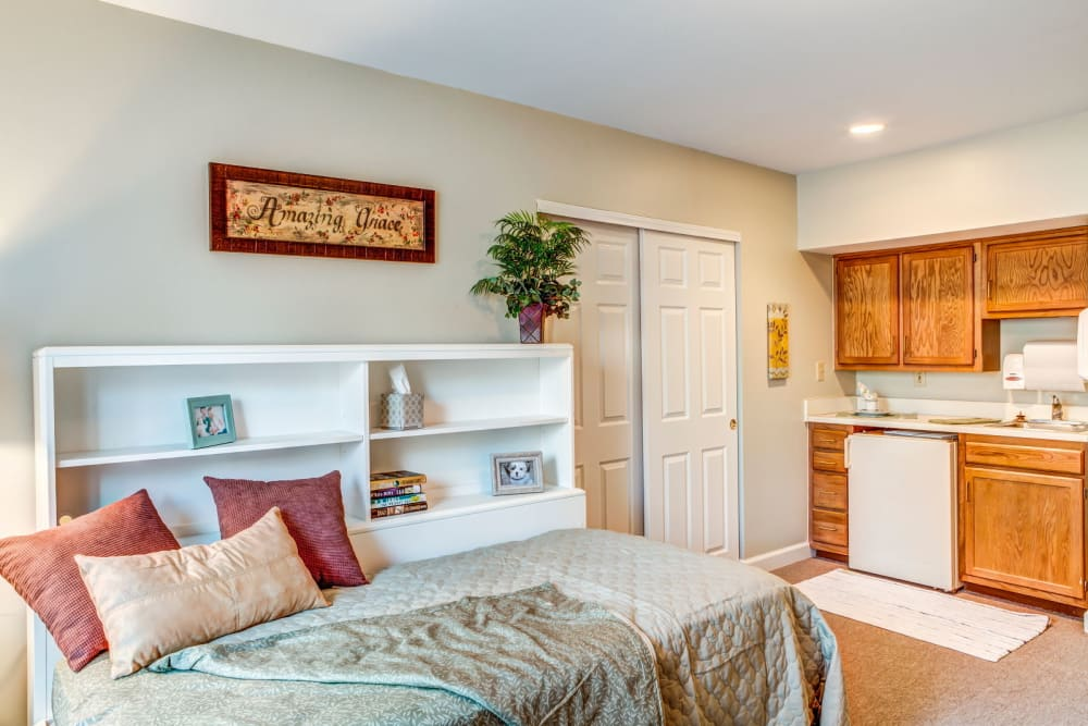 Cozy bed with wood accented kitchen in apartment at Carriage Court of Lancaster in Lancaster, Ohio