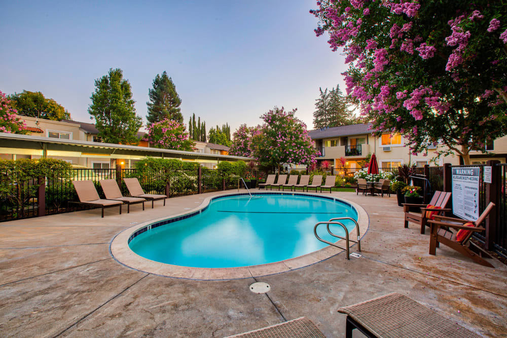 Lounge chairs near the pool at twilight at Pleasanton Place Apartment Homes in Pleasanton, California