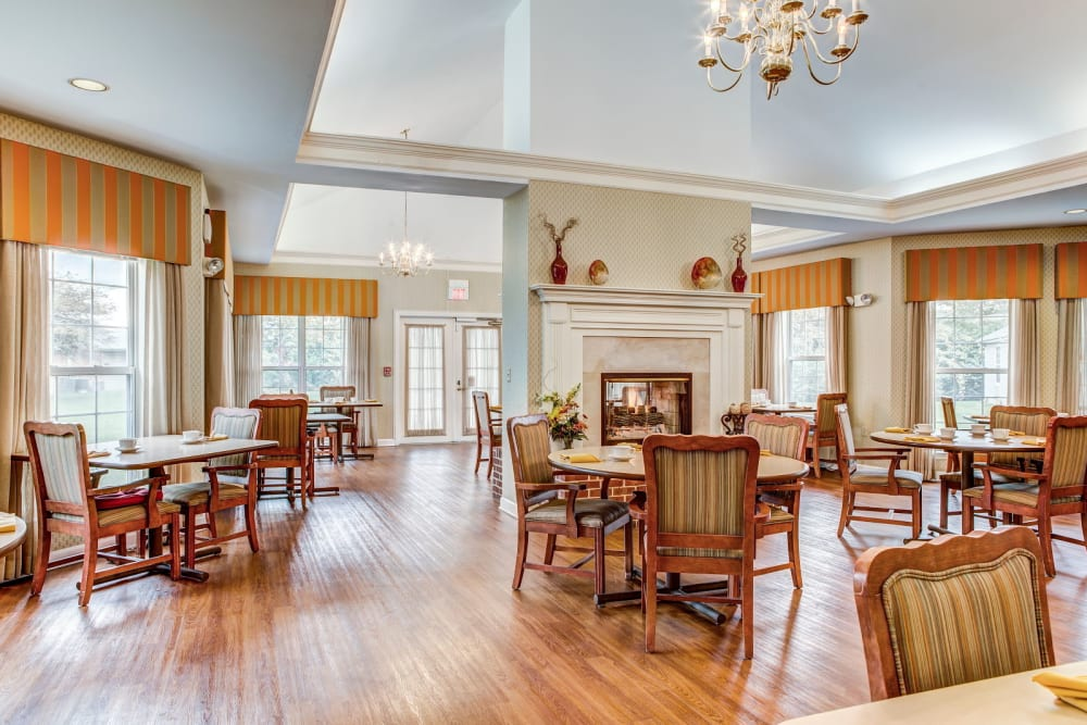 Elegant communal dining hall with wood accents and chandeliers at Carriage Court of Grove City in Grove City, Ohio
