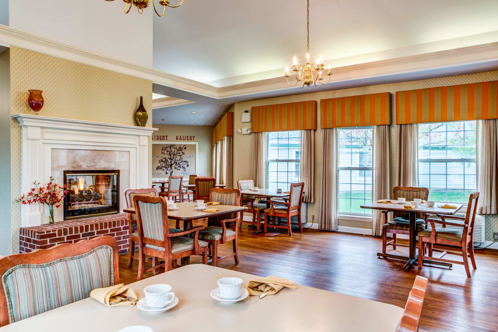 Commual dining area with elegant fireplace and wood accents at Carriage Court of Grove City in Grove City, Ohio