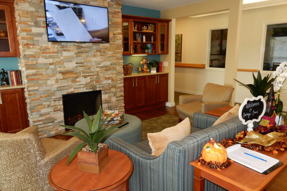 TV lounge area with comfy sofas and foliage at Carriage Court of Grove City in Grove City, Ohio