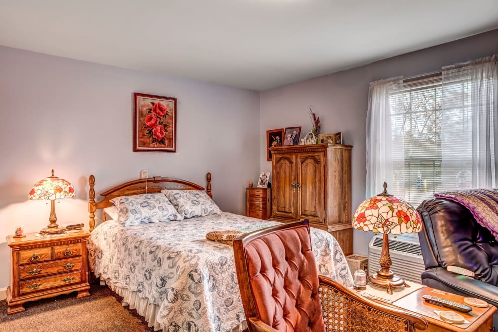 Cheerful bedroom in upscale senior living facility at Carriage Court of Grove City in Grove City, Ohio