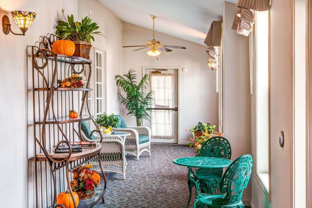 Sun room complete with elegant green seating and table at Grand Victorian of Sycamore in Sycamore, Illinois