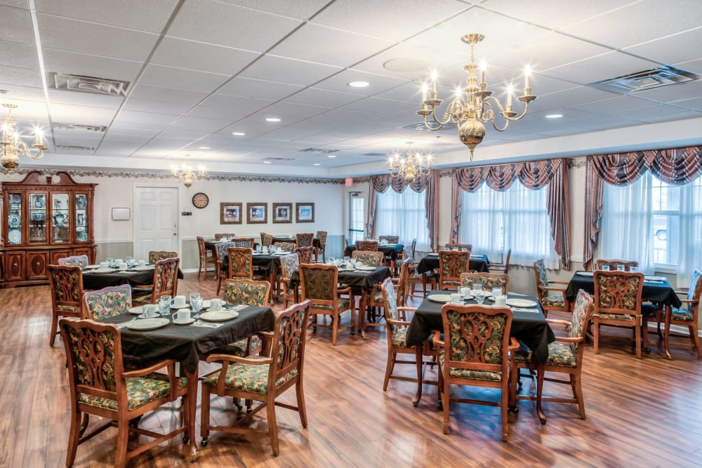 Elegant dining room with chandeliers and wood accents  at Grand Victorian of Sycamore in Sycamore, Illinois