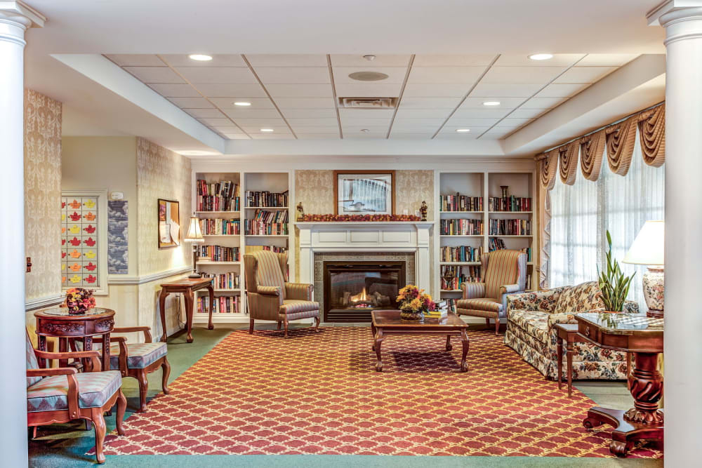 Cozy sitting room with fireplace and bookcases at Grand Victorian of Sycamore in Sycamore, Illinois