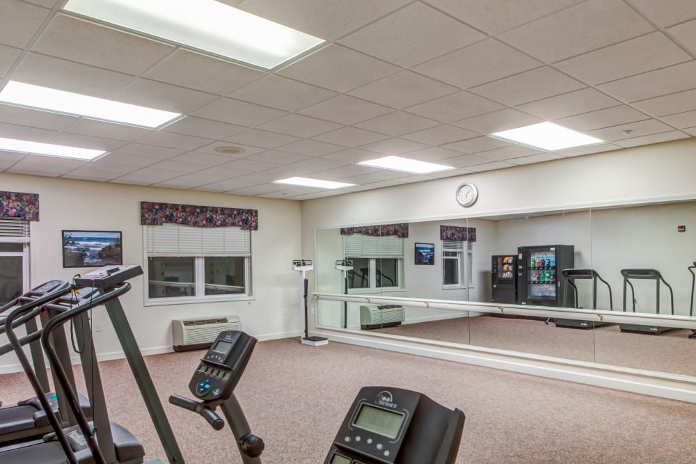 Deluxe gym with machinery and mirror at Grand Victorian of Sycamore in Sycamore, Illinois