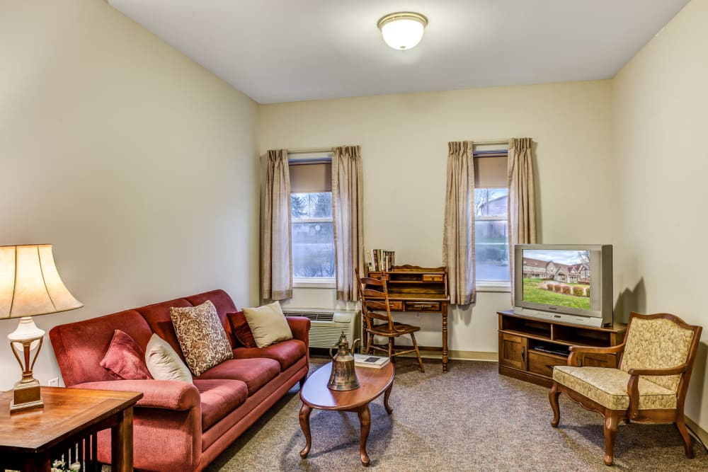 Well lit seating area of upscale senior living apartment at Grand Victorian of Sycamore in Sycamore, Illinois