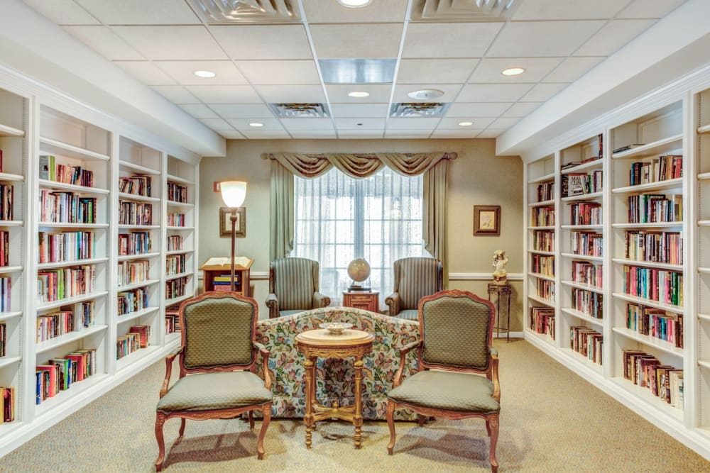 Comfortable lounge with seating and bookshelves at Grand Victorian of Rockford in Rockford, Illinois