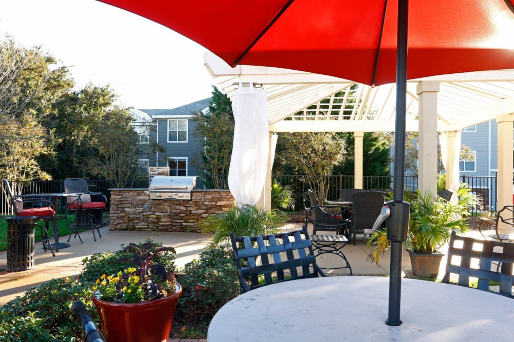Table with Seating and an Umbrella near BBQ Area at The Seasons at Umstead in Raleigh, North Carolina
