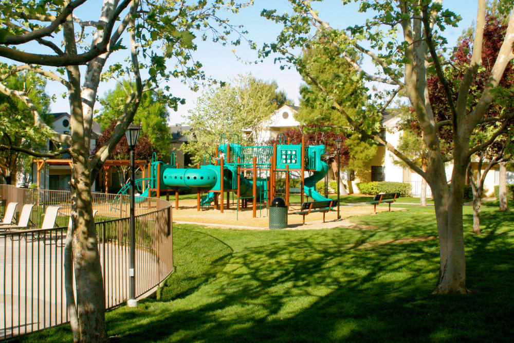 Onsite children's playground nestled among green grass and mature trees at Mountain Vista in Victorville, California