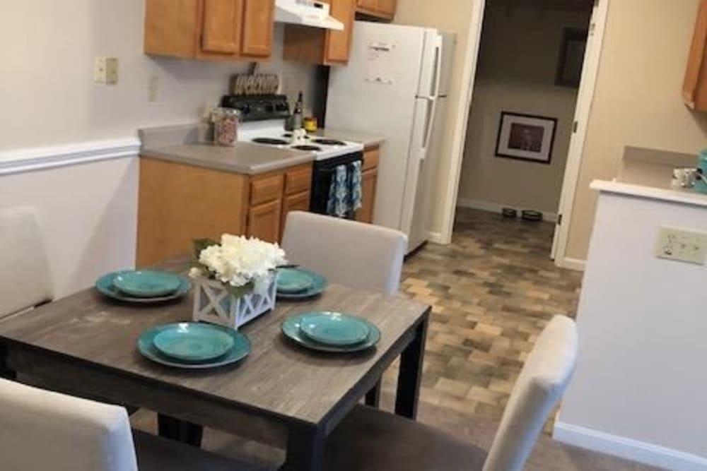 Kitchen and dining area with the table set at Aspen Pines Apartment Homes in Wilder, Kentucky