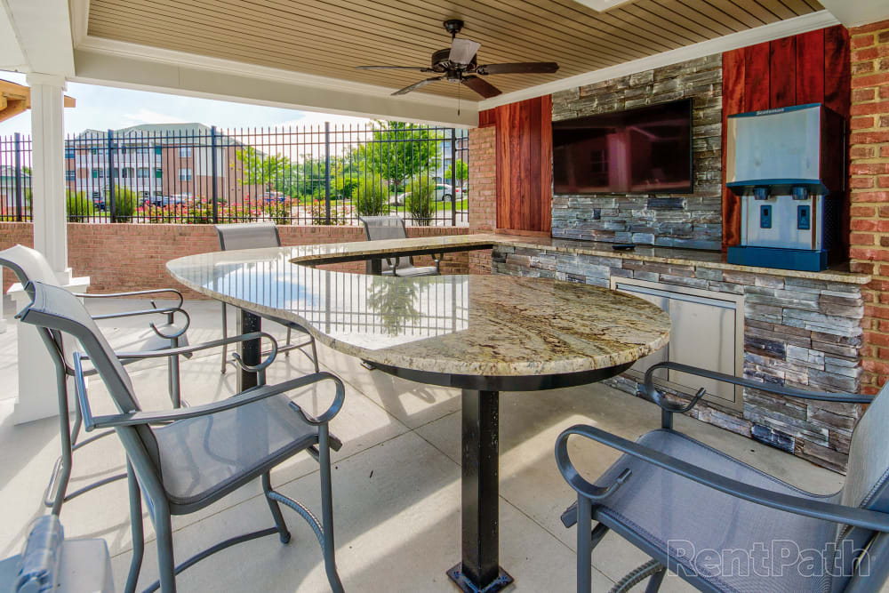 Table and chairs out by the pool to sit in after a swim at Aspen Pines Apartment Homes in Wilder, Kentucky