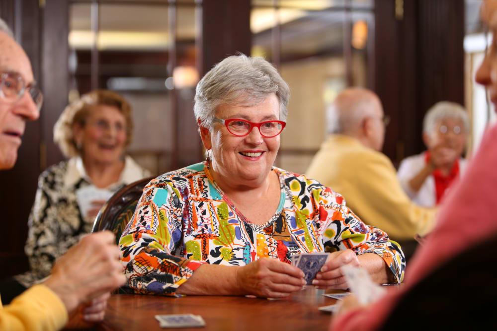 Happy senior living residents playing cards at Brookstone Estates of Charleston in Charleston, Illinois.