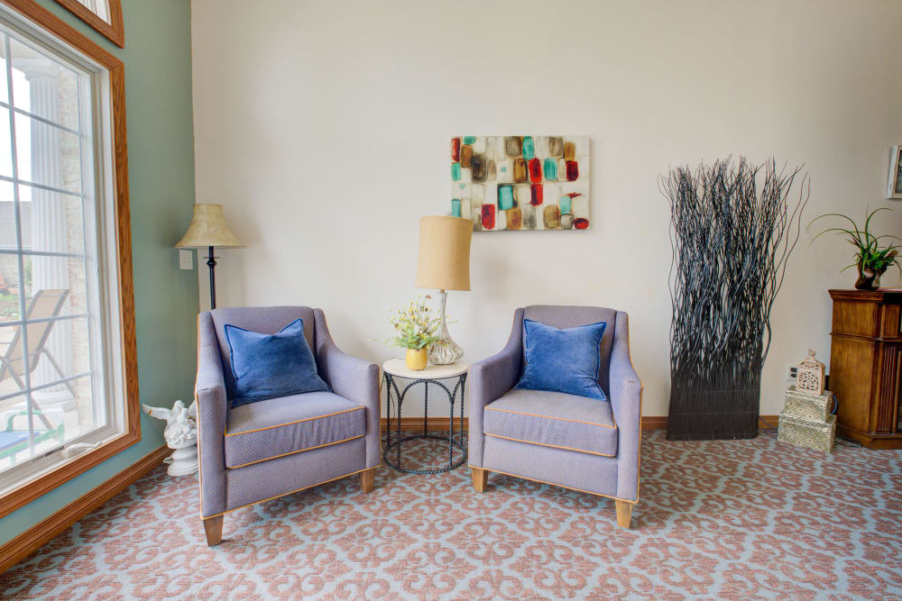 Welcoming chairs with blue cushions and artwork at Brookstone Estates of Vandalia in Vandalia, Illinois