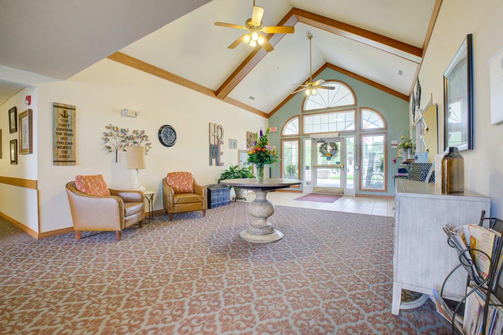 Bright hallway with seating and flowers at Brookstone Estates of Vandalia in Vandalia, Illinois