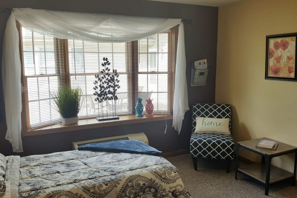 Charming apartment with bed and seating at Brookstone Estates of Robinson in Robinson, Illinois
