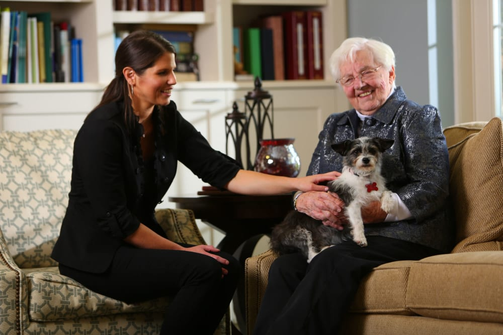 Friendly staff member with resident and her dog at Brookstone Estates of Robinson in Robinson, Illinois
