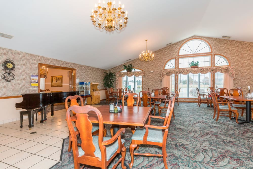Elegant wood dining room complete with chandeliers and piano at Brookstone Estates of Paris in Paris, Illinois