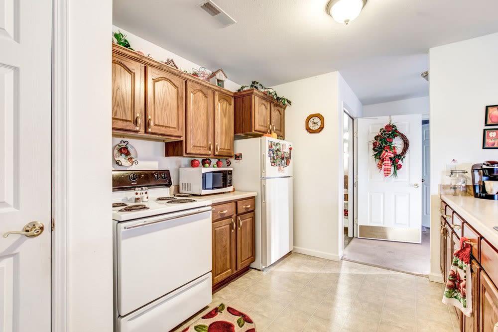 Kitchen with wood accents in senior living apartment at Brookstone Estates of Paris in Paris, Illinois