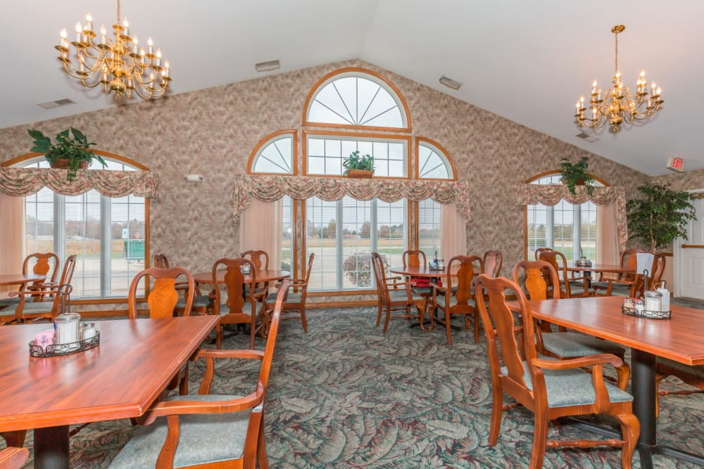 Elegant dining room with wood tables, large windows, and chandeliers at Brookstone Estates of Paris in Paris, Illinois