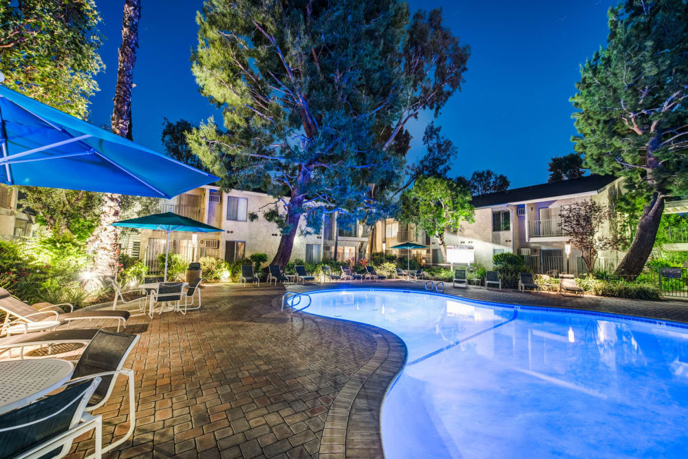 Swimming pool aglow with underwater lights in the early evening at Village Pointe in Northridge, California