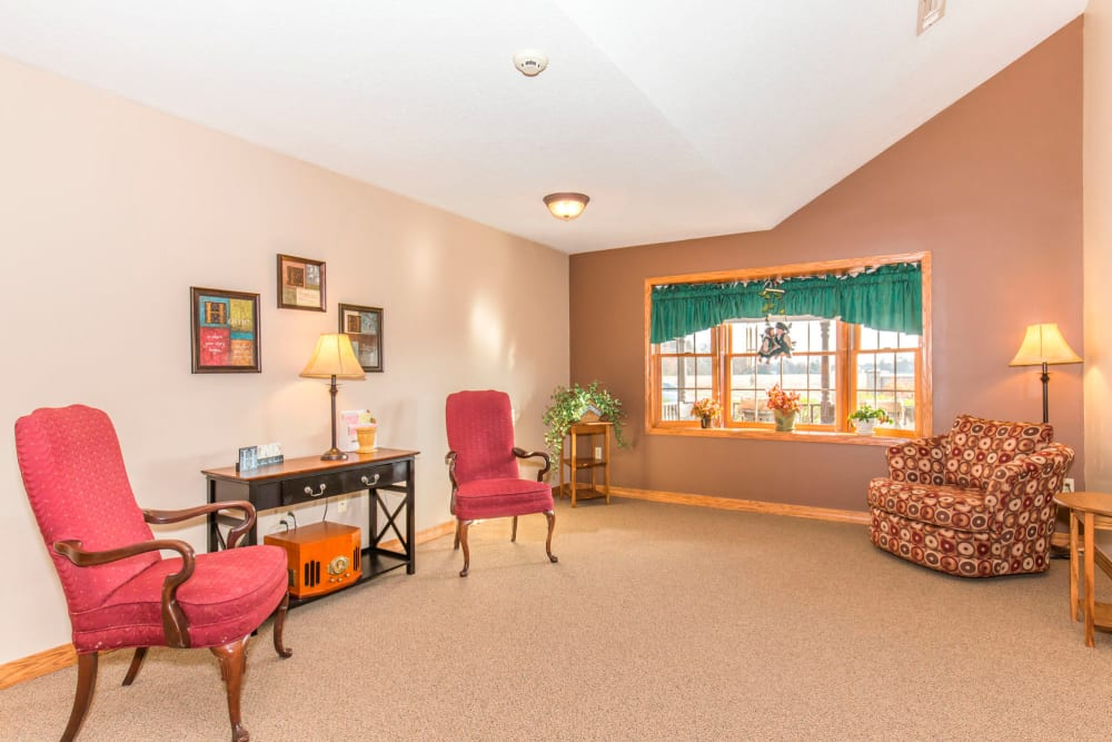 Comfortable lounge with elegant red chairs and window at Emerald Glen of Olney in Olney, Illinois
