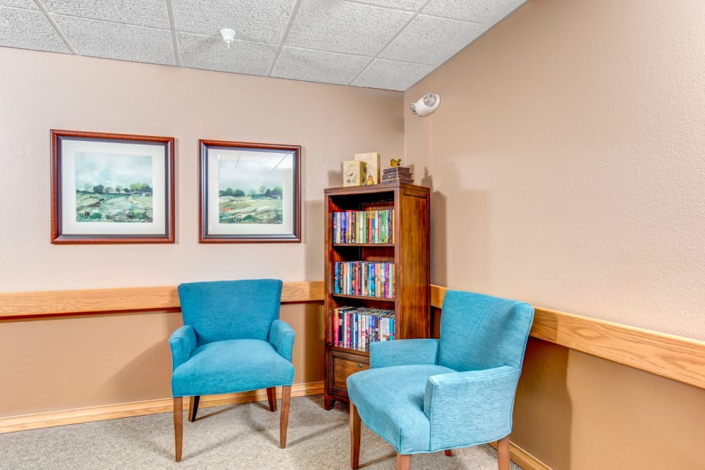 Library room with sky blue chairs and bookshelf at Brookstone Estates of Olney in Olney, Illinois