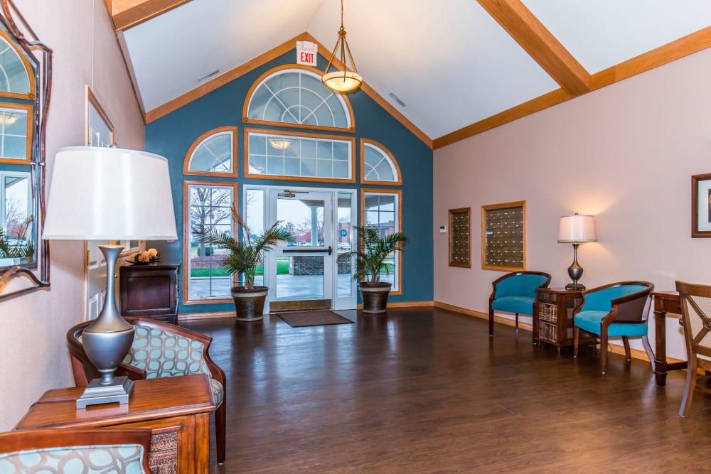 Sitting area with large window, foliage, and hardwood floor at Brookstone Estates of Olney in Olney, Illinois