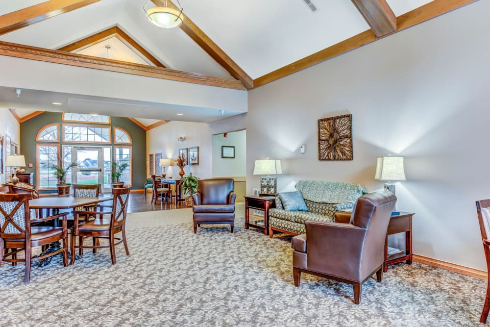 Cozy sitting room with wood accents and arm chairs at Brookstone Estates of Olney in Olney, Illinois
