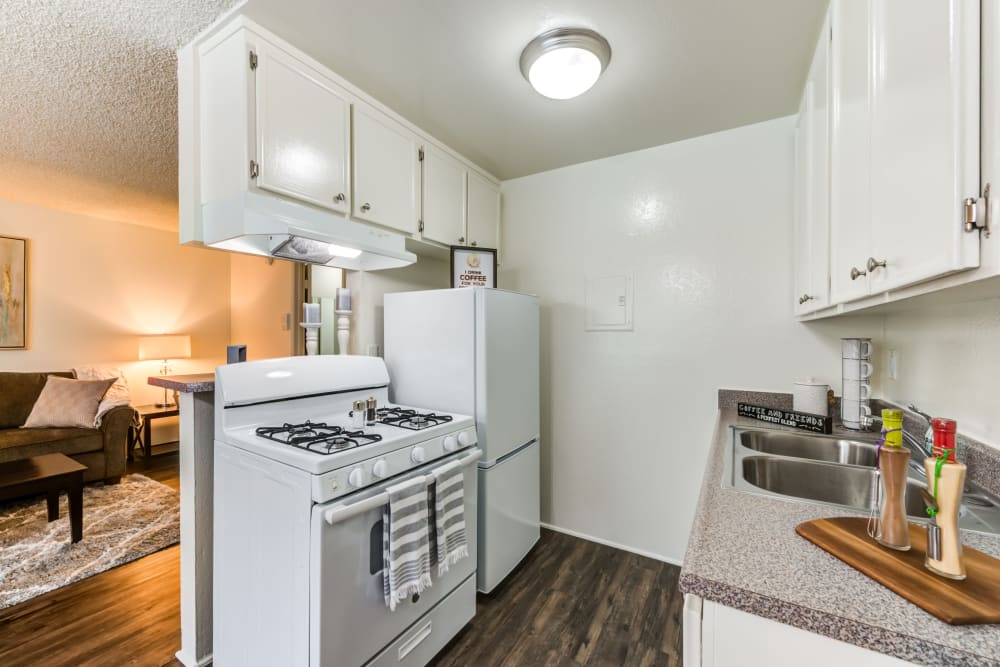 A kitchen with white appliances and white cabinetry at The Arbor in Studio City, California
