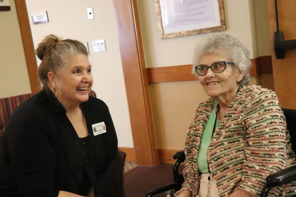 A caregiver and resident smiling at each other at The Springs at Mill Creek in The Dalles, Oregon