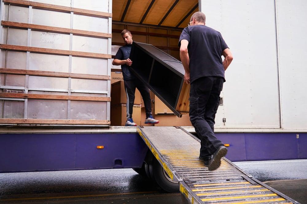 Two men loading furniture into a moving truck near A-American Self Storage in Reno, Nevada