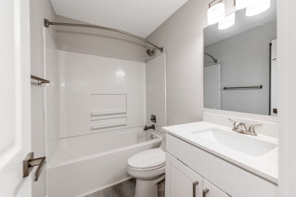 Bathroom with a shower bath combo and a clean mirror behind the sink at The Flats at Arrowood in Charlotte, North Carolina