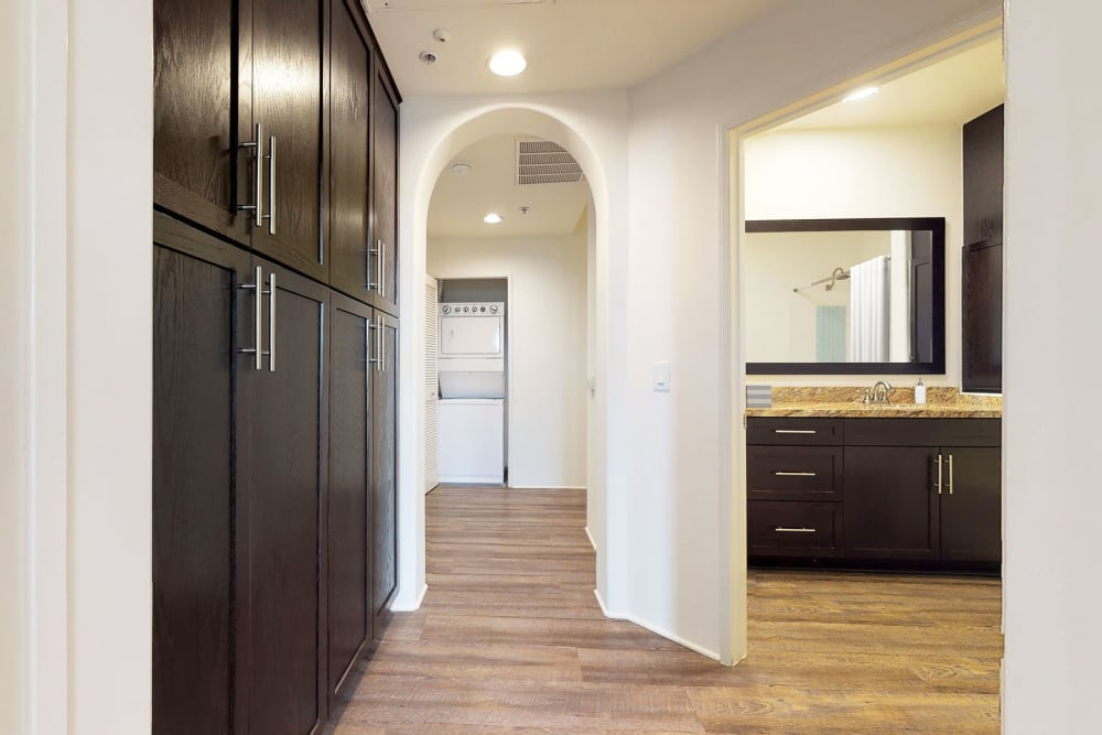 Rich espresso wood cabinetry providing extra pantry storage in a model home's hallway at L'Estancia in Studio City, California