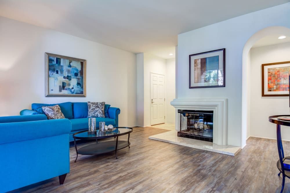 Beautiful hardwood flooring and a fireplace in a model home's living area at L'Estancia in Studio City, California