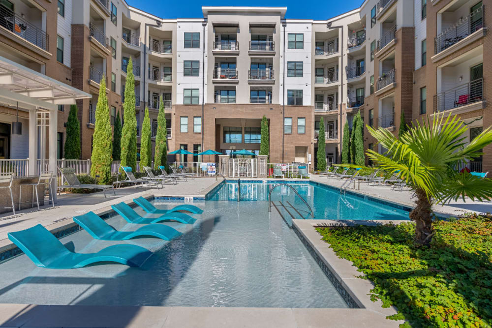 Sparkling resort style pool with deck lounge chairs in shallow pool area at Marq at Crabtree in Raleigh, North Carolina