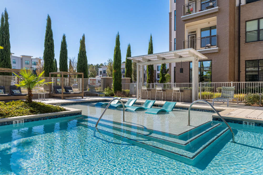 Sparkling resort style pool with deck lounge chairs at Marq at Crabtree in Raleigh, North Carolina